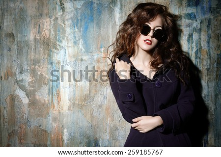 Close-up portrait of a sexual woman with beautiful curly hair alluring by the grunge wall. Fashion, beauty and love concept.