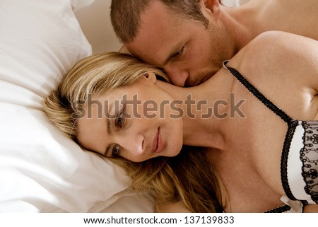 Close up portrait of a sexy couple laying down in bed, relaxing and kissing and having a romantic moment.