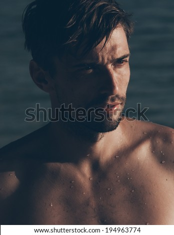 Close-up portrait of a sexy handsome Caucasian young man, bearded and tanned, posing shirtless while looking aside, in a hot sunny day at the seaside - stock photo