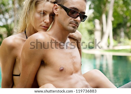 Close up portrait of a sexy young couple hugging while lounging on the edge of an exotic swimming pool in a tropical hotel destination, outdoors.