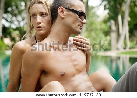 Close up portrait of a sexy young couple hugging while lounging on the edge of an exotic swimming pool in a tropical hotel destination, outdoors. - stock photo
