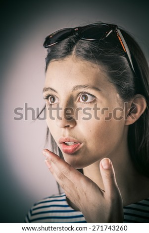 Close up Portrait of a Shocked Young Woman, Wearing Sunglasses on Top of her Head, with One Hand Close to his Face on a Gray Brown Gradient Background. - stock photo