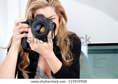 Close up portrait of a smart woman photographer taking a photograph with her professional digital photographic camera, focusing the lens while at her work desk office. - stock photo