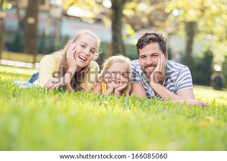 Close-up portrait of a smiley cute family lying on the grass and posing at camera on the foreground  - stock photo