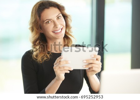 Close-up portrait of a smiling attractive businesswoman using her digital tablet at office desk.