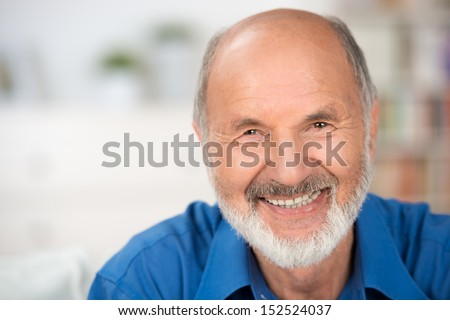 Close up portrait of a smiling attractive senior man looking directly at the camera with copyspace