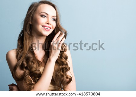 Close-up portrait of a smiling beautiful woman with long curly hair. - stock photo