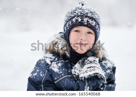 close up portrait of a smiling boy in the snowfall