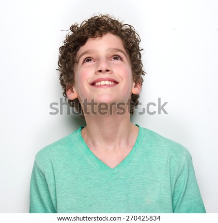 Close up portrait of a smiling boy looking up - stock photo