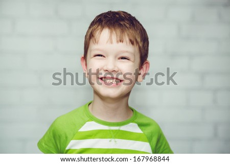 Close-up portrait of a smiling boy on a light background. - stock photo