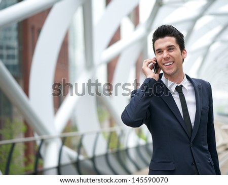 Close up portrait of a  smiling business man talking on mobile phone in the city - stock photo