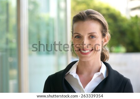 Close up portrait of a smiling business woman with black jacket and white shirt standing outside - stock photo
