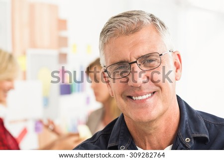 Close up portrait of a smiling businessman at office - stock photo