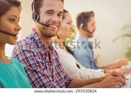 Close up portrait of a smiling businessman working in a call centre - stock photo