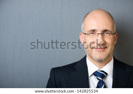 Close-up portrait of a smiling friendly mature balding businessman, wearing a suit and a necktie, leaning against a gray wall with copy-space - stock photo