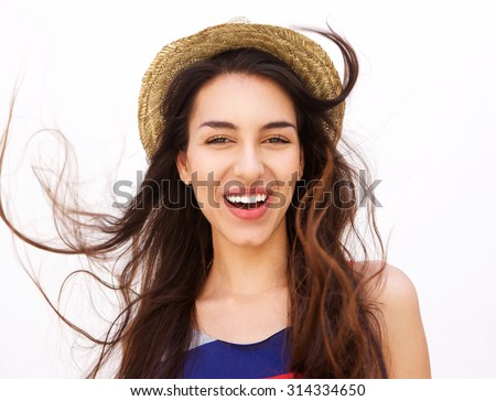 Close up portrait of a smiling girl with long hair and hat posing against white background