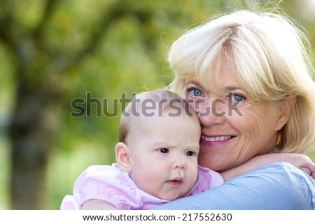 Close up portrait of a smiling grandmother holding baby granddaughter - stock photo