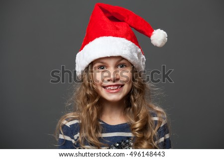 Close up portrait of a smiling little girl in a christmas cap, gray background