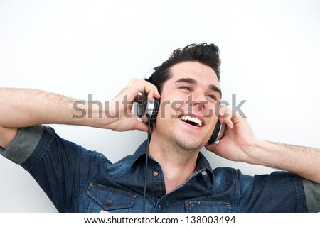 Close up portrait of a smiling man listening to music on headphones - stock photo