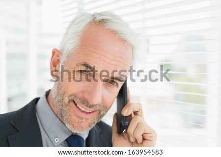 Close-up portrait of a smiling mature businessman using cellphone in office