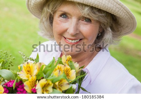 Close-up portrait of a smiling mature woman holding flowers at the park - stock photo