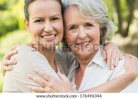 Close-up portrait of a smiling mature woman with adult daughter at the park - stock photo