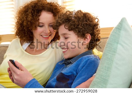 Close up portrait of a smiling mother sitting at home with her son - stock photo