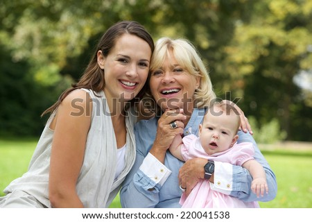 Close up portrait of a smiling mother sitting outdoors with grandmother and child - stock photo