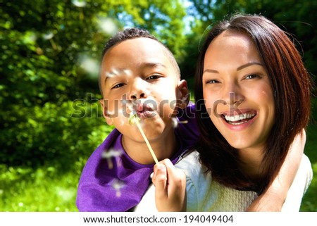 Close up portrait of a smiling mother with son blowing dandelion outdoors - stock photo