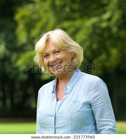 Close up portrait of a smiling senior woman outdoors - stock photo