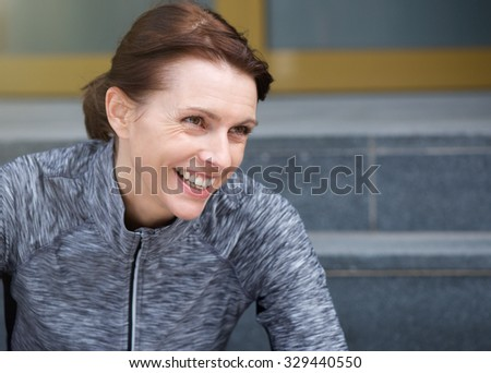 Close up portrait of a smiling sporty woman sitting outside  - stock photo