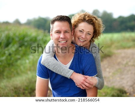 Close up portrait of a smiling woman hugging her boyfriend outdoors - stock photo