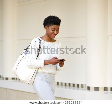 Close up portrait of a smiling woman sending text message on mobile phone - stock photo