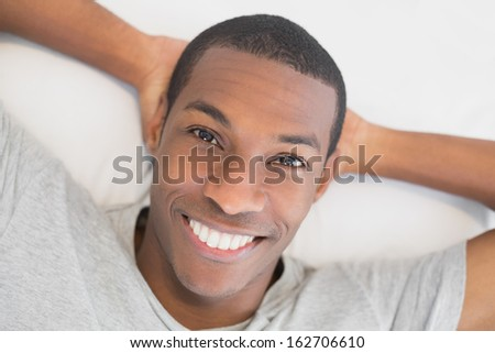 Close up portrait of a smiling young Afro man resting in bed at home - stock photo