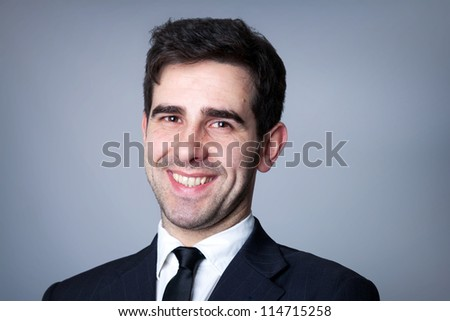 Close-up portrait of a smiling young business man on grey background - stock photo