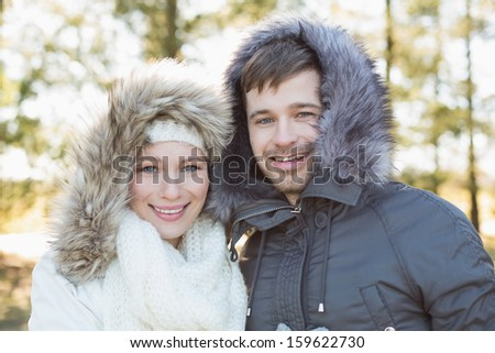 Close-up portrait of a smiling young couple in fur hood jackets in the woods