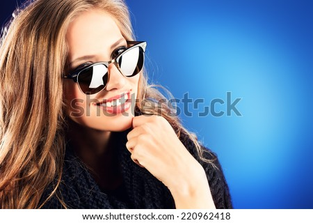 Close-up portrait of a smiling young lady with beautiful hair wearing black sunglasss.