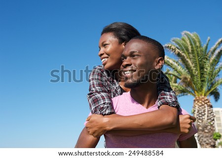 Close up portrait of a smiling young man carrying girlfriend on back  - stock photo