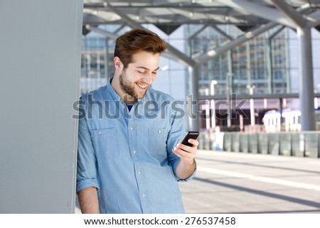 Close up portrait of a smiling young man looking at mobile phone - stock photo