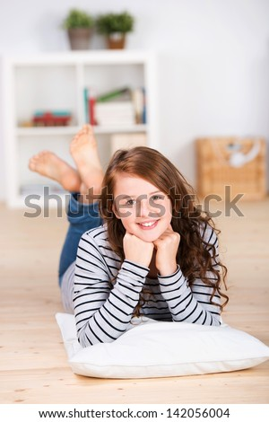 Close-up portrait of a smiling young teenage girl laying on the floor of her home on her stomach over a pillow with bare-feet raised and crossed - stock photo