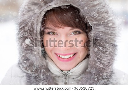 Close-up portrait of a smiling young woman in warm clothing