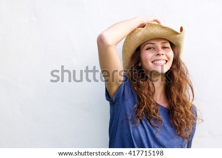 Close up portrait of a smiling young woman with cowboy hat - stock photo