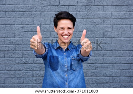 Close up portrait of a smiling young woman with thumbs up gesture - stock photo