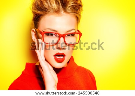 Close-up portrait of a stunning female model in red dress and elegant spectacles posing over yellow background. Beauty, fashion, optics. - stock photo