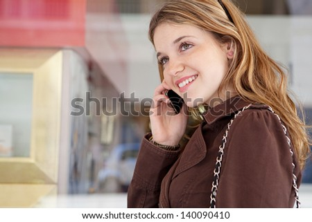 Close up portrait of a teenage girl in a shopping street, standing by a store glass window with reflections in the city, having a cell phone conversation and smiling holding her smartphone. - stock photo