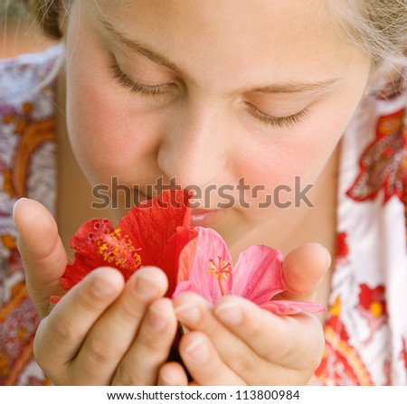 Close up portrait of a teenage girl smelling hibiscus flowers. - stock photo