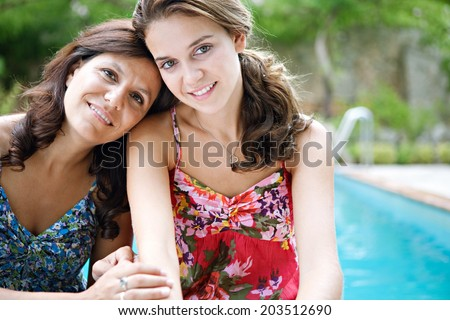 Close up portrait of a teenager daughter and her mother hugging and smiling during a summer holiday break in a vacation villa green garden and swimming pool, relaxing together. Outdoors lifestyle. - stock photo