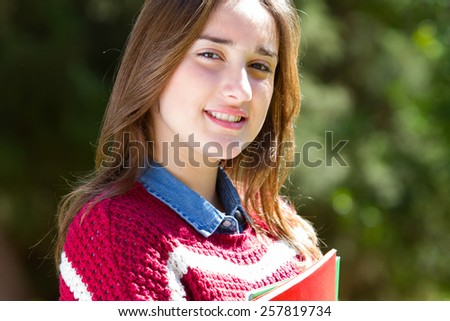 Close-up portrait of a teenager holding books outside the campus - stock photo