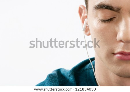 Close up portrait of a teenager's half face closing his eyes while listening to music with his headphones against a white background. - stock photo