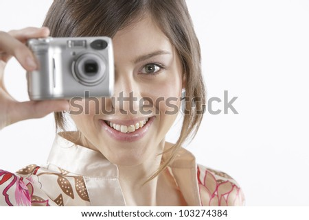 Close up portrait of a teenager taking a picture with her digital camera. - stock photo